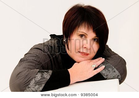 Beautiful attractive mature woman with head leaning on hands