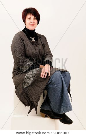 Beautiful attractive mature woman sitting in blue jeans and coat