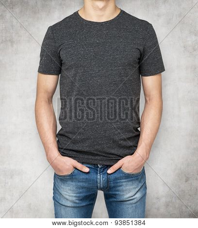 Man Wearing Dark Grey T-shirt, Concrete Background. Hands In The Pockets.