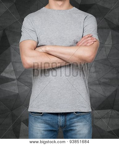 Man Wearing Grey T-shirt With Crossed Hands, Isolated On Dark Concrete Background.