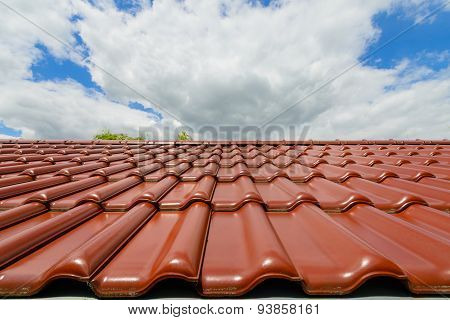 Close-up of glazed brown roof tiles against the background of a cloudy sky poster