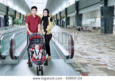 Family In The Airport Hall With Baby On The Pram