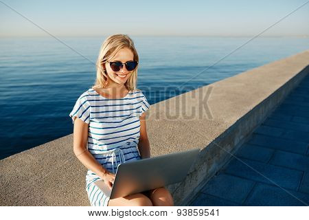 Beautiful Young Woman Sitting On Beach With Laptop Smiling And Communicates Over The Internet Via Wi