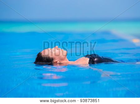 Young woman enjoying water and sun in outdoor swimming pool.
