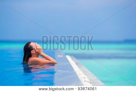Young woman enjoying water and rest in outdoor swimming pool