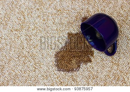 Coffee spilled from the cup on the carpet
