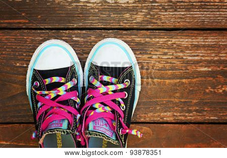 Boise, ID - JUNE 19, 2015: an instagram type image of low top converse sneakers on a wooden deck. converse, made by chuck taylor is a very popular shoe for urban hipsters and skaters
