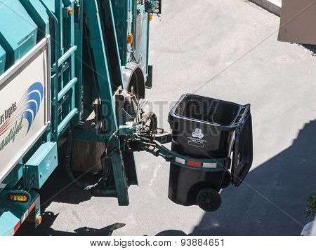 LOS ANGELES, CALIFORNIA, USA - July 13, 2010:  City of Los Angeles Department of Sanitation automated trash truck arm at work.