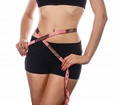 Young slim woman measuring waist after exercising. Isolated on white background. The concept of losing excess weight. poster