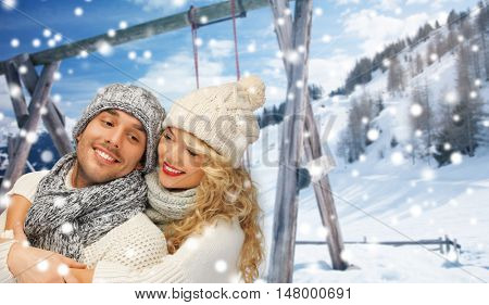 people, christmas, holidays and season concept - happy family couple in winter clothes hugging over wooden swing and snowy mountains background