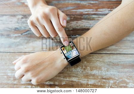 business, modern technology, media, internet and people concept - close up of female hands setting smart watch with news web page on screen on wooden table