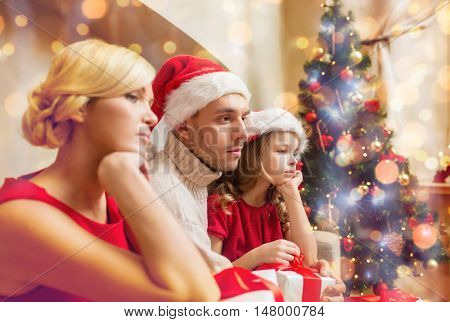 family, christmas, x-mas, winter and people concept - unhappy family at home with many gift boxes