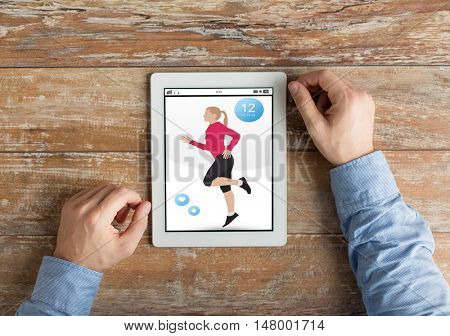 sport, people and technology concept - close up of male hands with fitness application on tablet pc computer on wooden table