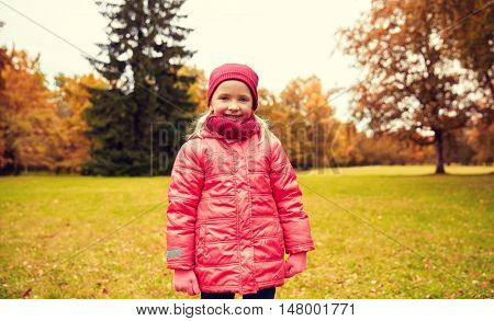 autumn, childhood, nature and people concept - happy little girl in park