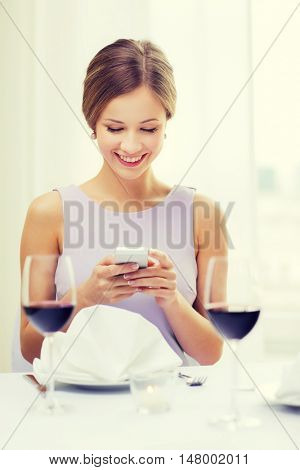 reastaurant, technology and happiness concept - smiling young woman with smartphone and glass of red wine at restaurant