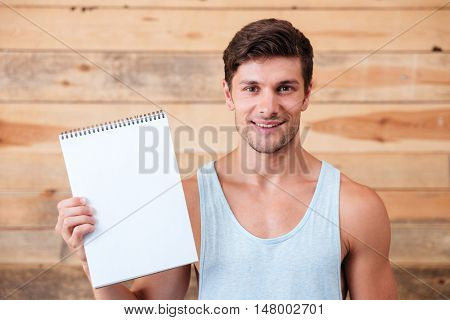 Smiling young casual man showing blank notebook isolated on a wooden background