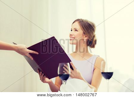 reastaurant and happiness concept - smiling young woman recieving menu from waiter at restaurant