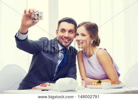 restaurant, couple, technology and holiday concept - smiling couple taking self portrait picture with digital camera at resaturant