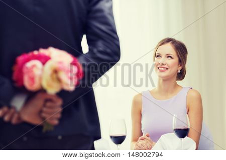 restaurant, couple and holiday concept - smiling young woman looking at man with flower bouquet behind the back