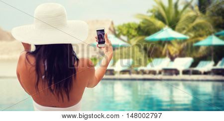 lifestyle, leisure, summer, technology and people concept - smiling young woman or teenage girl in sun hat taking selfie with smartphone over beach and swimming pool background