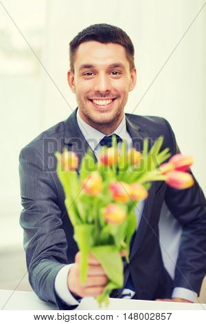 spring, flowers and happiness concept - smiling handsome man giving bouquet of fresh flowers