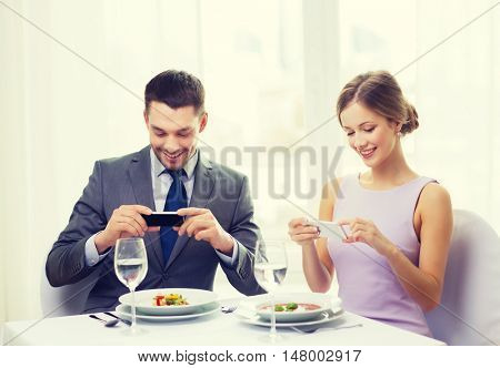 restaurant, couple, technology and holiday concept - smiling couple taking picture of appertizer with smartphone camera at restaurant