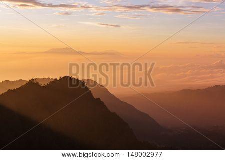 Fabulous light of sun rays at beautiful sunrise in mountains of Java island, Indonesia