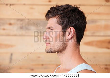 Side view portrait of a young man in t-shirt over wooden background
