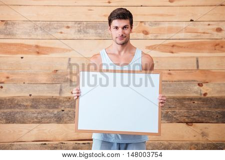Casual young man holding blank board over wooden background and looking at camera