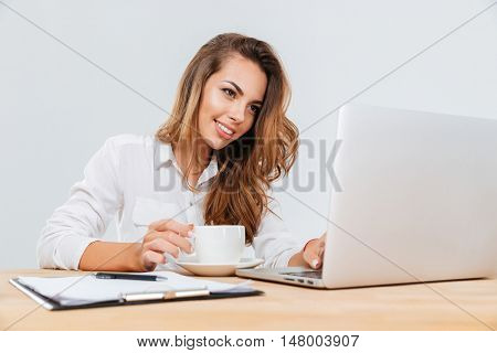 Cheerful cute young businesswoman with cup of coffee sitting and using laptop over white background