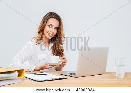 Cheerful beautiful young businesswoman drinking coffee at workplace over white background