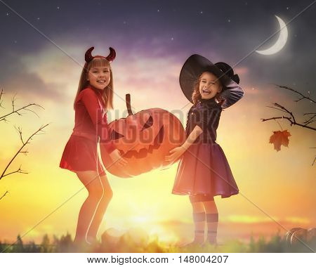Two happy sisters on Halloween. Funny kids in carnival costumes outdoors. Cheerful children and pumpkin on sunset background.