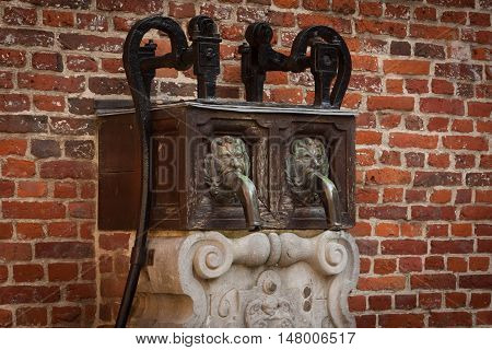 Old fountain near the brick wall in Grand Beguinage in Leuven. Belgium. Flanders.