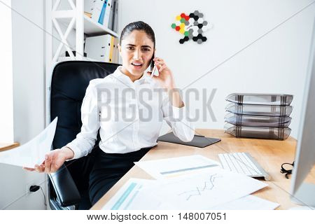 Concentrated beautiful businesswoman talking on the phone while sitting at workplace at office