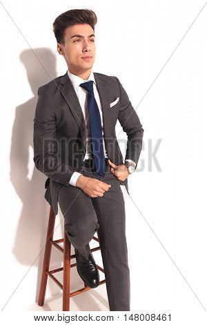 man in suit and tie sitting and looking up in studio on white background