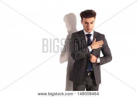 young business man in solemn pose with hand on chest, on white studio background