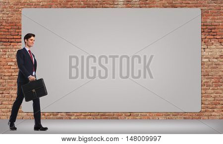 happy smiling business man holding a suitcase is walking by a big blank billboard