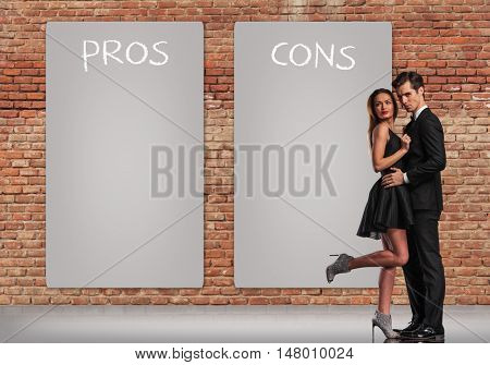 pros and cons in a relationship, young elegant couple standing embraced near big posters