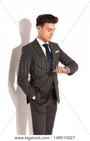 young business man cheking time on his watch, studio picture on white wall