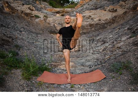 Bold man doing yoga outdoors on rocks
