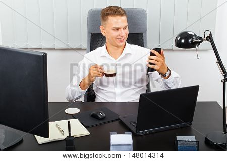 Handsome young businessman making video call and drinking his coffee