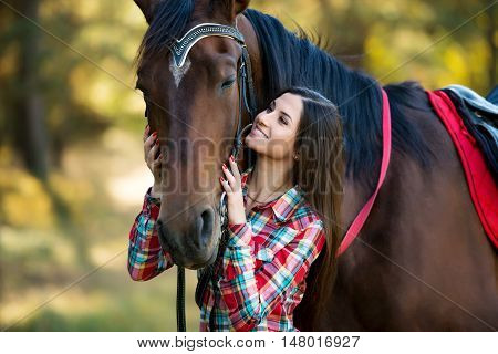 beautiful long hair young woman posing with a horse outdoor