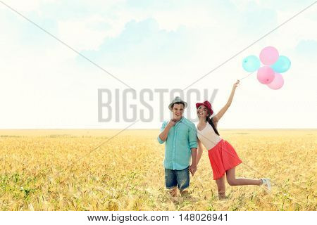 Young couple with toy air balloons on a field
