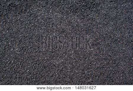 Background asphalt just applied on the roadway. This is the wearing course which is applied regularly because worn by vehicular traffic