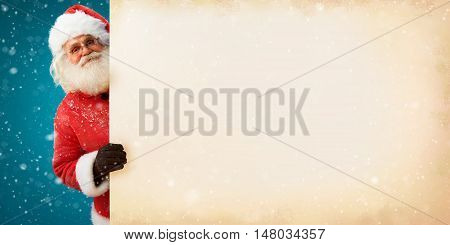 Jolly Santa Claus peeking out of an old paper banner with space for Your Text. Merry Christmas & New Year's Eve concept. Close up on blurred blue background.
