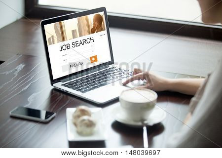 Attractive young woman sitting in cafe with cup of coffee and cakes working on laptop computer searching for job using online web service. View over the shoulder. HR recruitment career concept