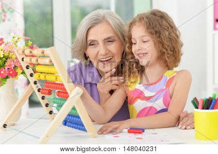 Cute little girl making homework with granny poster