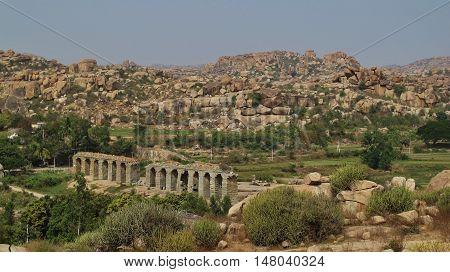 Old bridge and granite mountains in Hampi Karnataka. Popular travel destination in India.