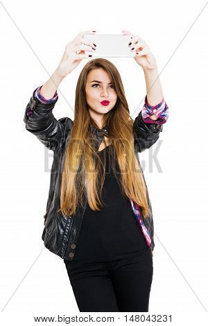 Millennial teenage girl posing taking a selfie on smart phone. Cool beautiful young woman with long blonde hair making faces posing for self portrait. Isolated on white background, medium retouch.