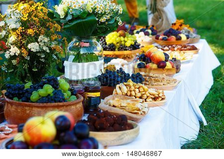 Meals on table of abundance as a part of natural wedding ceremony held in nature